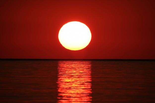 Tiro de largo alcance del mar que refleja el sol con el cielo rojo