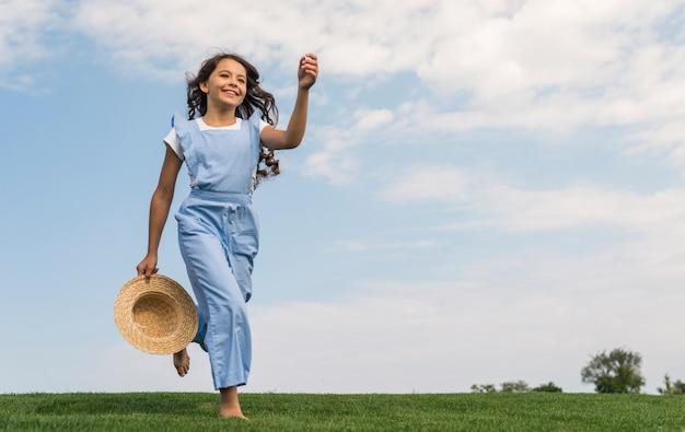 Tiro largo alegre niña corriendo sobre la hierba