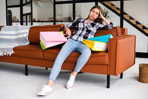 Tiro largo decepcionado mujer sentada en el sofá con bolsas