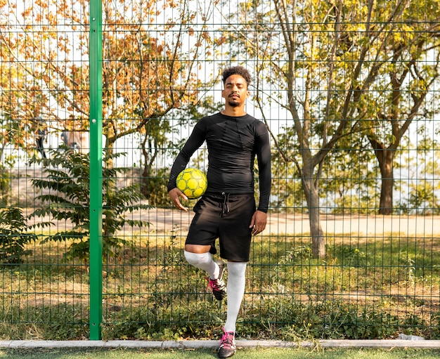 Tiro largo hombre afroamericano posando con una pelota de fútbol
