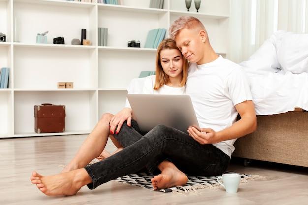 Tiro largo hombre y mujer mirando una película en la computadora portátil