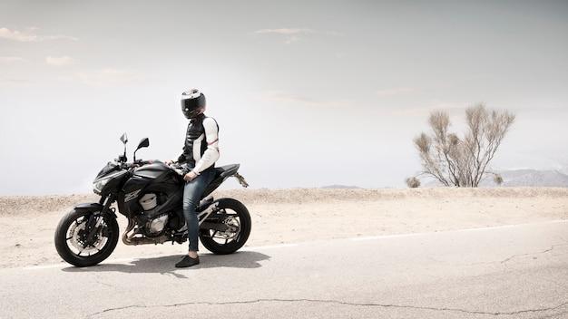 Tiro largo motociclista hombre sentado en moto