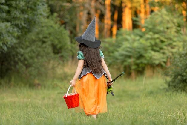 Tiro largo de niña con disfraz de halloween de bruja en la naturaleza