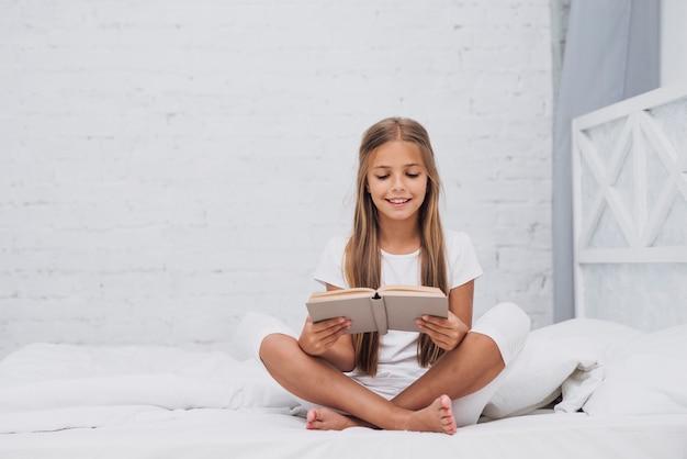 Tiro largo niña rubia leyendo un libro