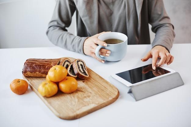 Tiro lateral del ángulo de manos femeninas con la manicura que toca la tableta digital. estudiante desayunando antes de ir a la universidad, tomando una taza de té y comiendo mandarinas con pastel enrollado, ella misma se horneó