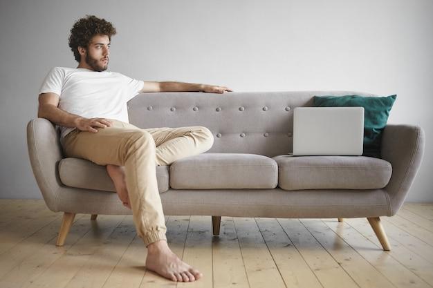 Tiro lateral de atractivo joven varón caucásico con barba espesa que usa una computadora portátil para trabajar, navegar por internet, leer artículos y navegar por sitios web, sentado cómodamente en un sofá gris
