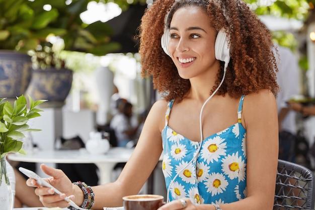 Tiro lateral de hermosa mujer afroamericana bastante sonriente sostiene un teléfono móvil moderno, escucha transmisiones de radio en línea, usa auriculares grandes blancos