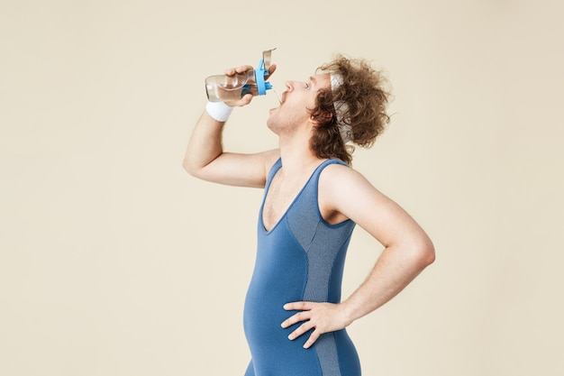 Tiro lateral del hombre sediento bebiendo agua de botella de vidrio