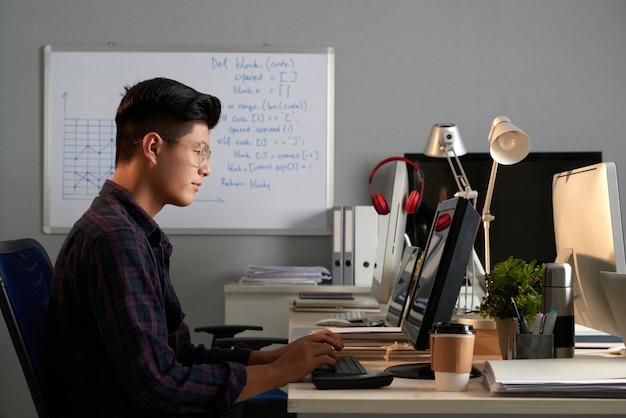 Tiro lateral del joven asiático en gafas trabajando en la computadora en la oficina