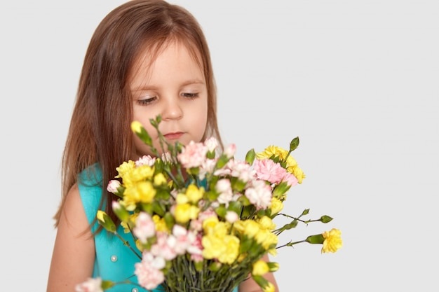 Tiro lateral de linda niña pequeña con cabello largo, disfruta de un agradable olor a flores, vestida con un elegante vestido azul, aislado en blanco con espacio de copia para su promoción o texto