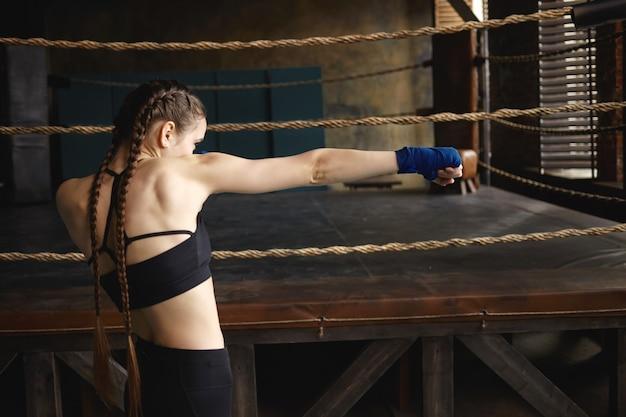 Tiro lateral de una mujer joven seria y decidida con fuertes brazos musculosos y dos trenzas golpeando el aire frente a ella como si estuviera boxeando contra un oponente invisible.