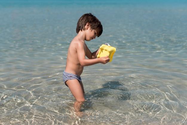 Tiro lateral de un niño jugando con un cubo de arena en el agua