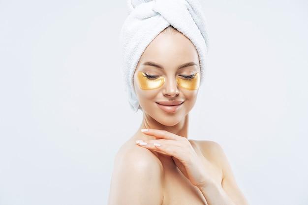 Tiro lateral de una tierna joven con almohadillas de colágeno dorado para los ojos, piel fresca y saludable, máscara hidratante antienvejecimiento, toca el hombro suavemente, usa una toalla de baño en la cabeza, aislada sobre una pared blanca de estudio