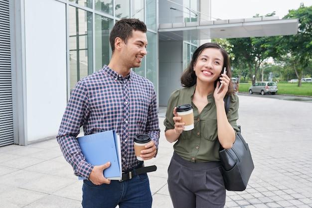 Tiro de longitud media de dos compañeros de trabajo de pie con tazas de café para llevar al aire libre, mujer haciendo una llamada telefónica