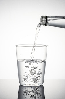 Tiro de macro de agua vertida en un vaso
