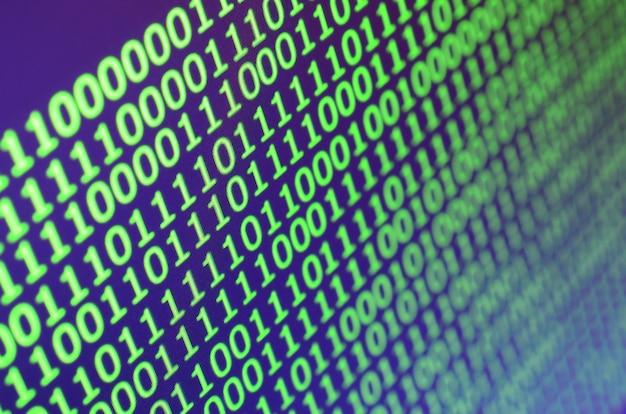 Tiro macro del código binario en el monitor de una computadora de oficina.