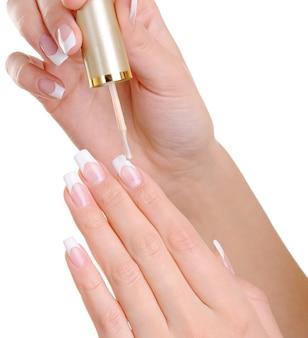 Tiro de macro de manos femeninas aplicando uñas claras desaparecen en sus uñas