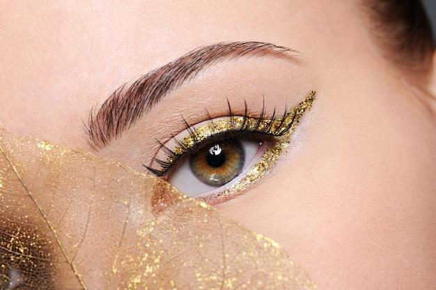 Tiro de macro de ojo femenino de belleza con maquillaje delineador de ojos dorado cubierto de hoja amarilla artificial