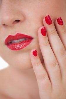 Tiro de macro de uñas pintadas de rojo de mujer joven y labios rojos