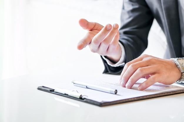 Tiro de la mano del empresario apuntando hacia delante mientras está sentado en la mesa blanca