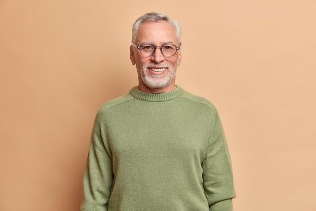 Tiro de media longitud de hombre mayor alegre sonríe felizmente con dientes blancos lleva gafas ópticas y un suéter aislado sobre una pared marrón