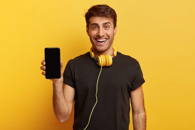 Tiro de media longitud de hombre optimista sostiene teléfono inteligente con pantalla simulada