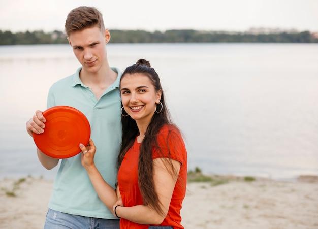 Tiro medio amigos sonrientes con frisbee rojo