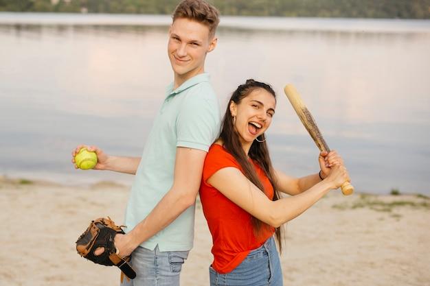 Tiro medio amigos sonrientes posando con equipo de béisbol