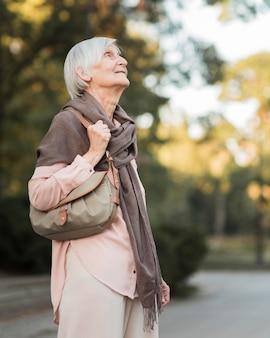 Tiro medio anciana admirando la naturaleza