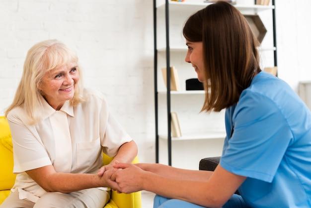 Tiro medio anciana y enfermera cogidos de la mano