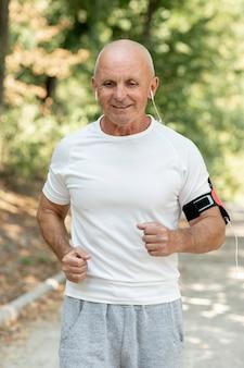 Tiro medio anciano corriendo escuchando música