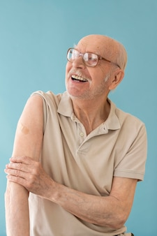 Tiro medio anciano sonriente después de la vacuna