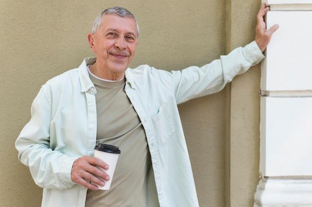 Tiro medio ancianos sosteniendo la taza de café