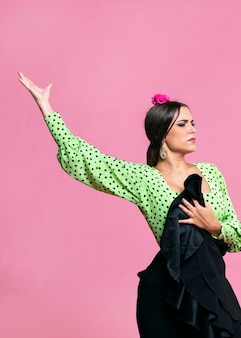 Tiro medio bailarina de flamenco levantando la mano