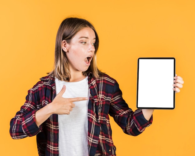 Tiro medio chica sorprendida apuntando a una tableta