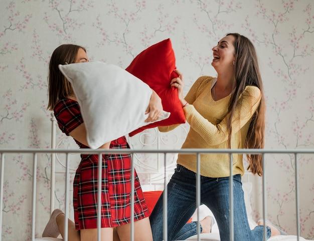 Tiro medio chicas felices en una pelea de almohadas