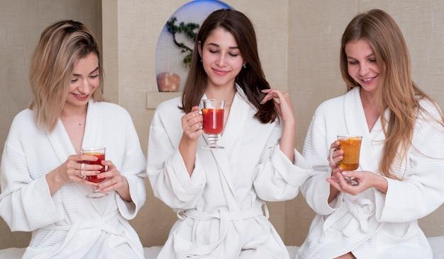 Tiro medio chicas lindas con bebidas en el interior