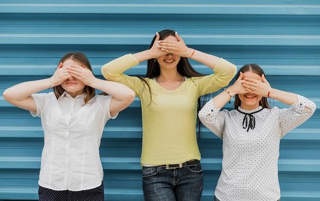 Tiro medio chicas sonrientes cubriendo sus ojos