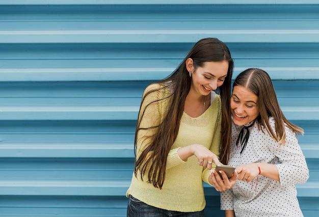 Tiro medio chicas sonrientes mirando smartphone