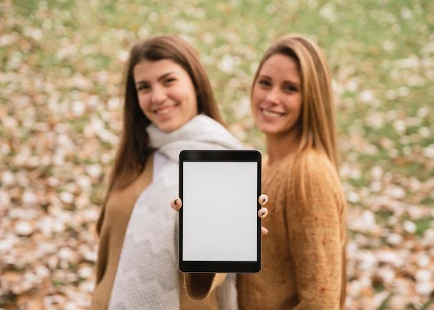 Tiro medio dos mujeres sonrientes sosteniendo la tableta en las manos
