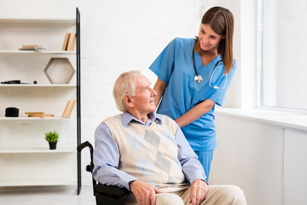 Tiro medio enfermera mirando anciano