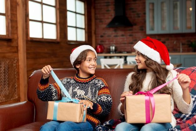 Tiro medio feliz hermano y hermana abriendo regalos