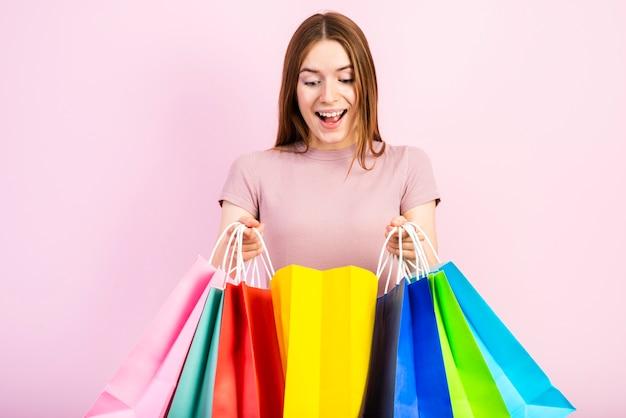 Tiro medio feliz mujer sosteniendo bolsas