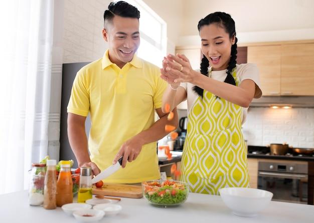 Tiro medio feliz pareja cocinando