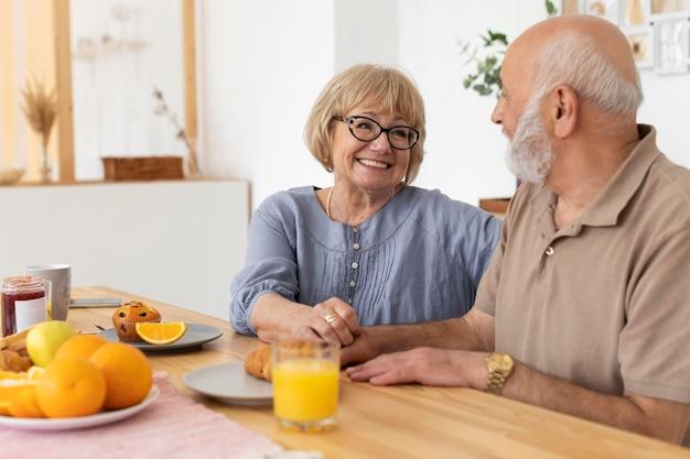 Tiro medio feliz pareja senior en la mesa
