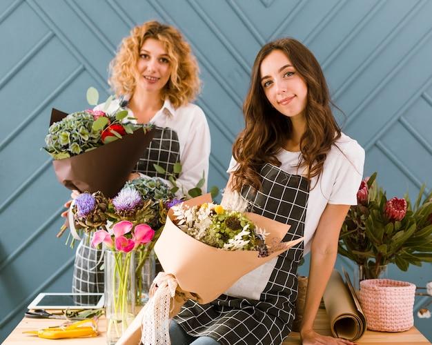 Tiro medio floristas posando con flores