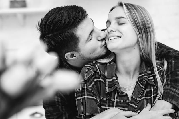 Tiro medio hombre besando a mujer en la mejilla en escala de grises