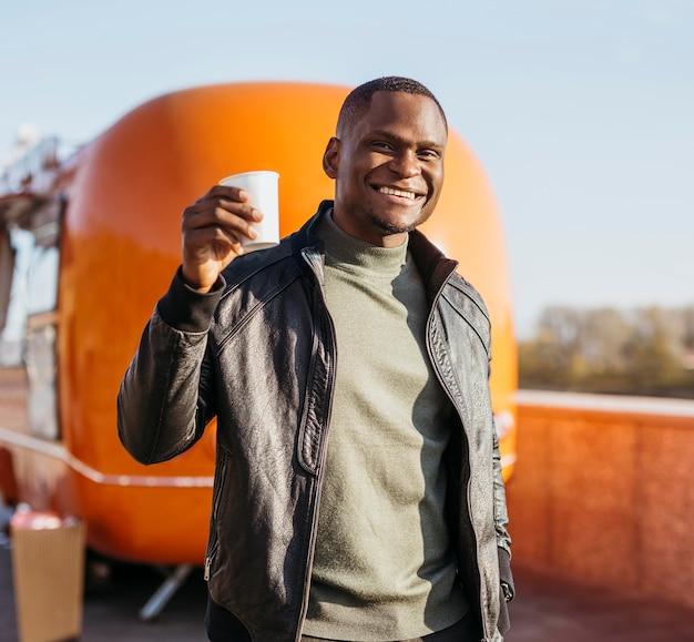 Tiro medio hombre feliz sosteniendo la taza de café frente al camión de comida
