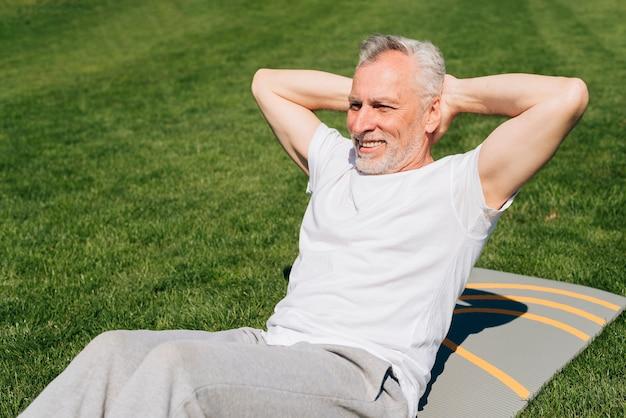 Tiro medio hombre haciendo abdominales sobre una estera