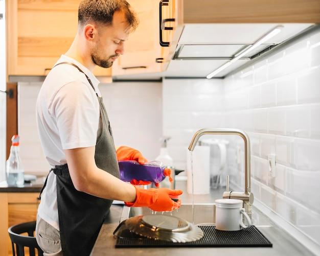 Tiro medio hombre lavando platos